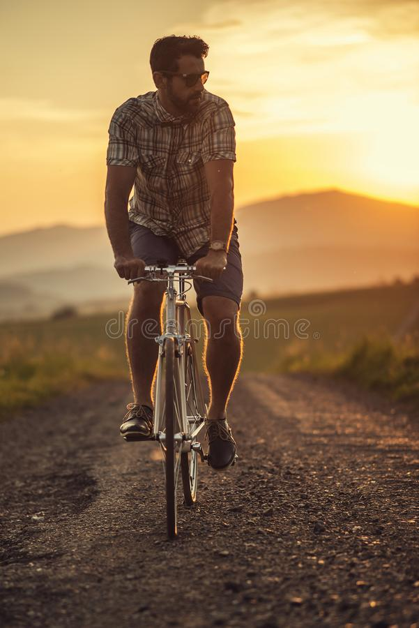 Young man with retro bicycle in sunset on the road, fashion photography on retro style with bike.  stock photography
