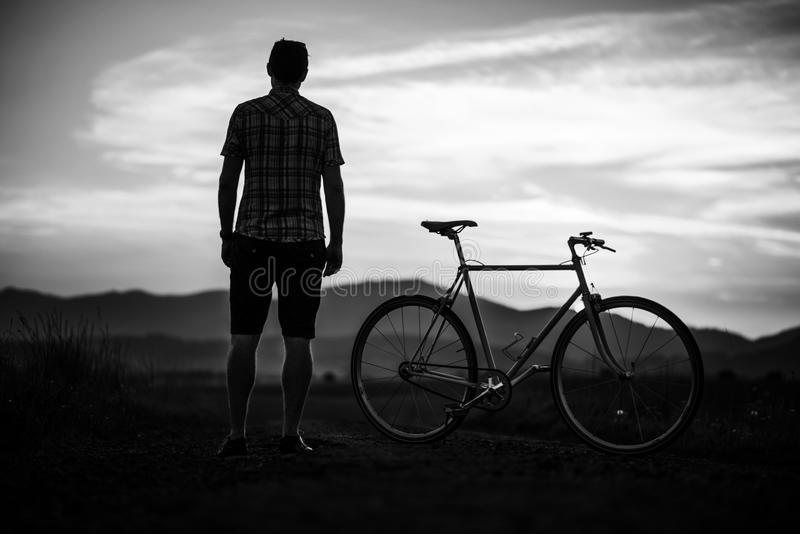 Young man with retro bicycle in sunset on the road, fashion photography on retro style with bike.  royalty free stock image