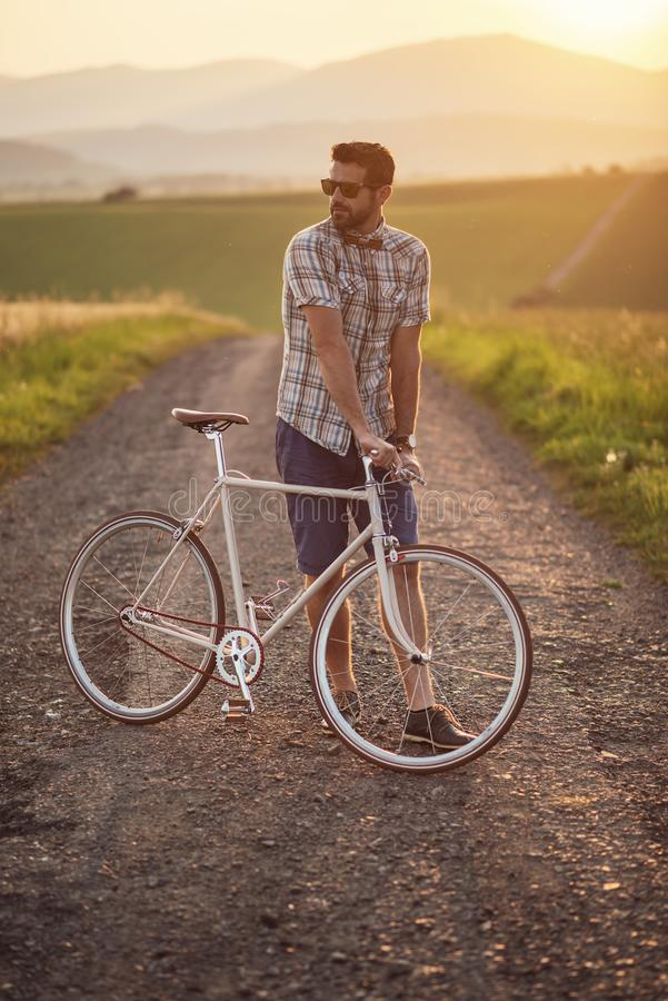 Young man with retro bicycle in sunset on the road, fashion photography on retro style with bike.  stock image