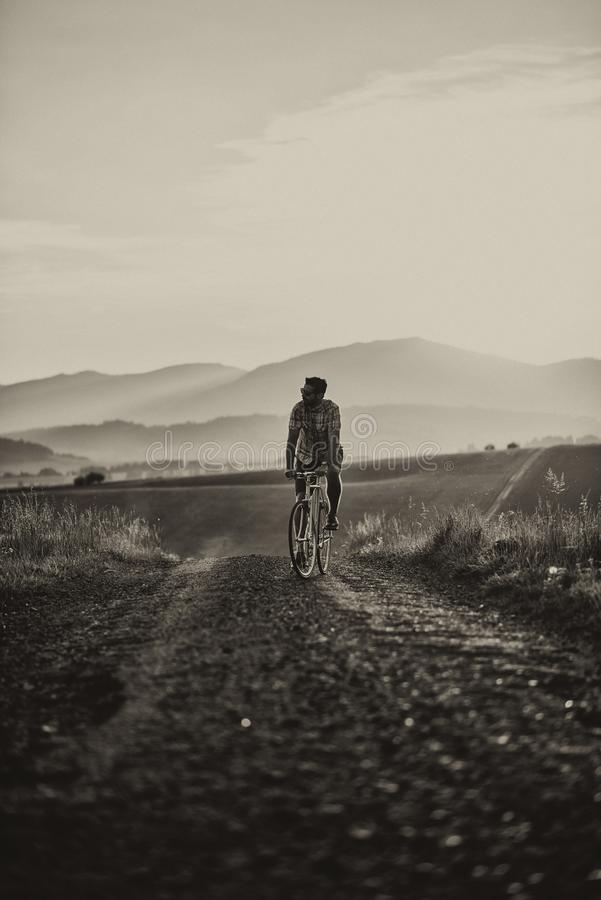 Young man with retro bicycle in sunset on the road, fashion photography on retro style with bike.  stock photo
