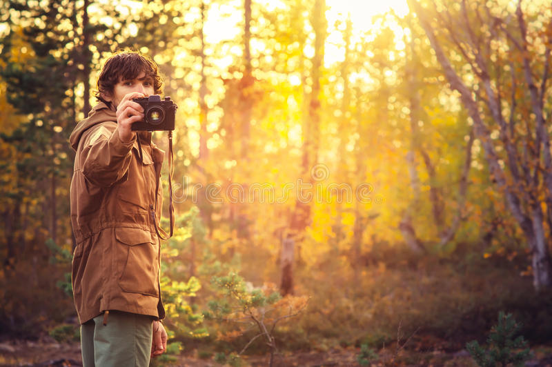 Young Man with retro photo camera outdoor hipster Lifestyle. Sunset forest nature on background royalty free stock image