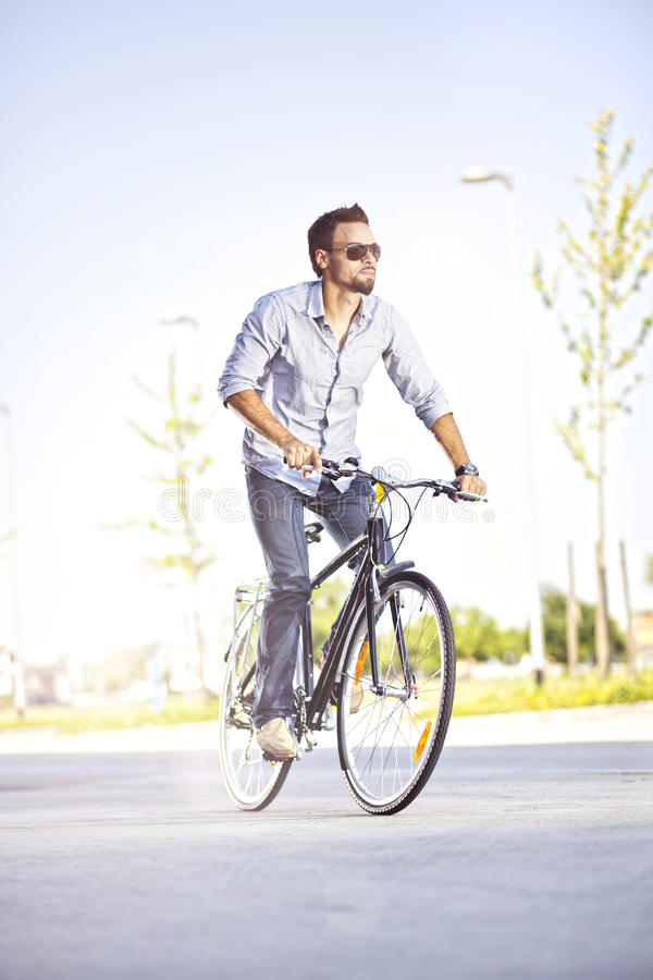Download Young man riding a bicycle stock image. Image of fast - 26093685