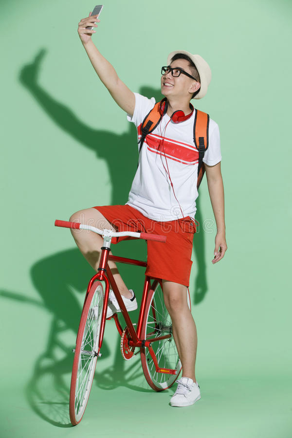 Young man riding a bicycle. The young man on background stock photos