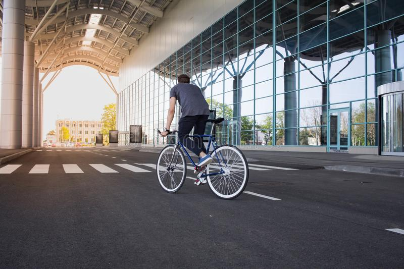 young man riding on bicycle in city street. Man on blue bicycle with white wheels, big mirror windows background stock images