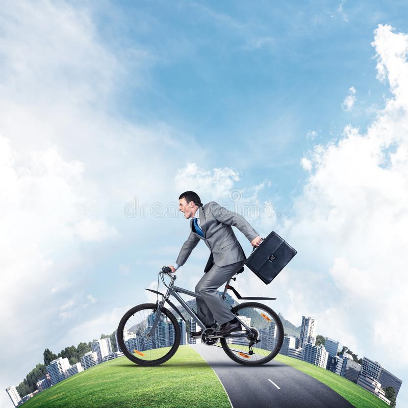Young man riding bicycle on highway. Young man riding bicycle on road. Businessman on bike hurry to work. Corporate employee wearing business suit with suitcase royalty free stock photos