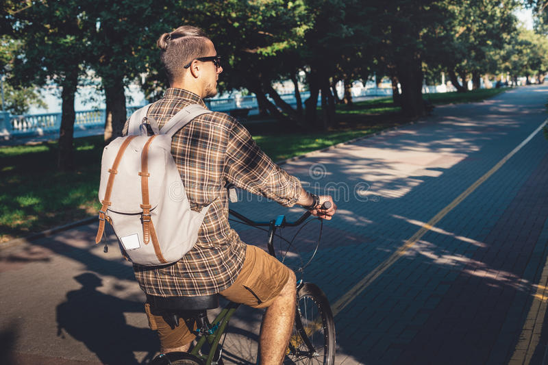 Young Man Riding On Bicycle In Summer Park, Cyclist In motion, Rear View. Lifestyle Urban Resting Concept. Young Man In Sunglasses With Backpack Riding On stock photo