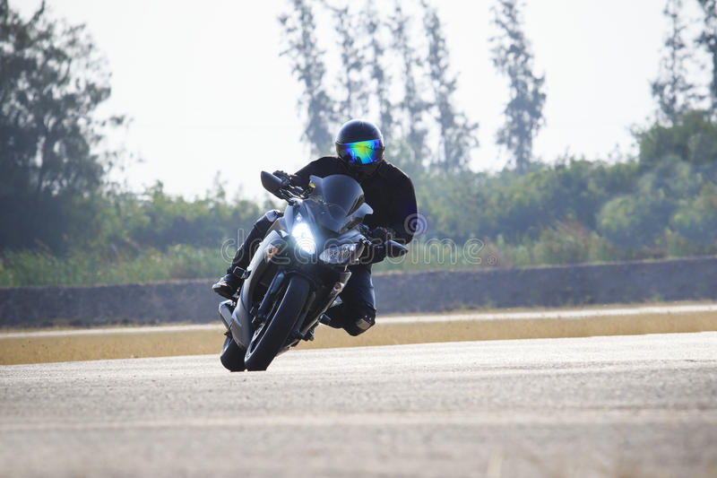 Young man riding big bike motorcycle against sharp curve of asphalt high ways road with rural lake scene use for male adventure ac. Tivities and motor sport stock photo