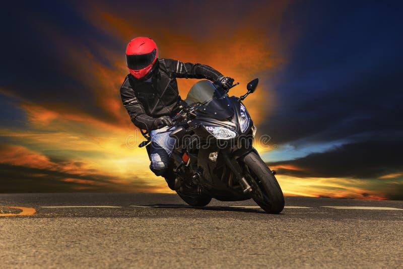 Young man riding big bike motorcycle on asphalt roads royalty free stock photo