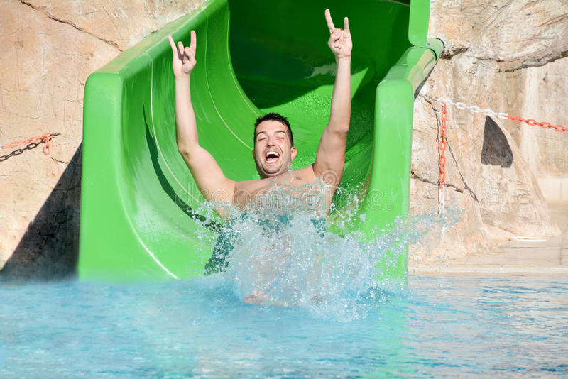 Young man riding down a water slide-man enjoying a water tube ride. Happy man coming out a tube ride at the water park and falling into the blue pool with a big stock photo