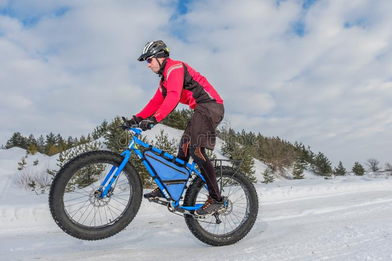 Fat bike. Fat tire bike. A young man riding fat bicycle in the winter. A young man riding fat bicycle in the winter. winter biking. Fatbike. Fat tire bike royalty free stock photos