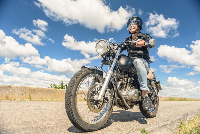 Young man riding his motorbike on open road stock photography