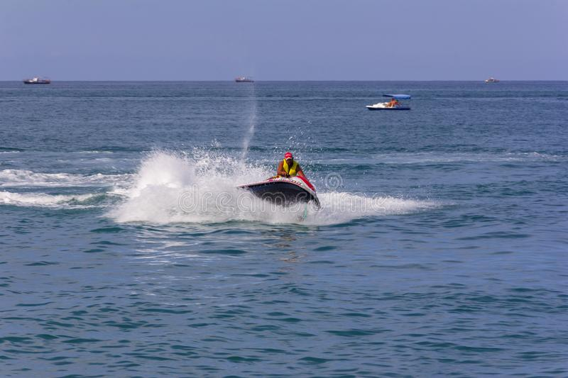 Young man riding a hydrocycle in the sea. Sochi, Russia - August 22, 2018: young man riding a hydrocycle in the sea royalty free stock photography