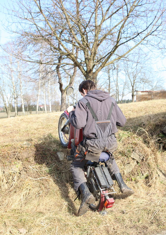 Young man riding motorbike. Young man in black clothes riding motorbike on grass slope stock image
