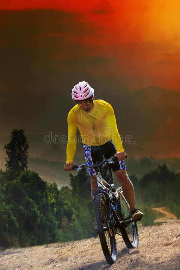 young man riding mountain bike bicycle crossing mountain hill jungle track with dusky sky scene use for out door sport and stock photo