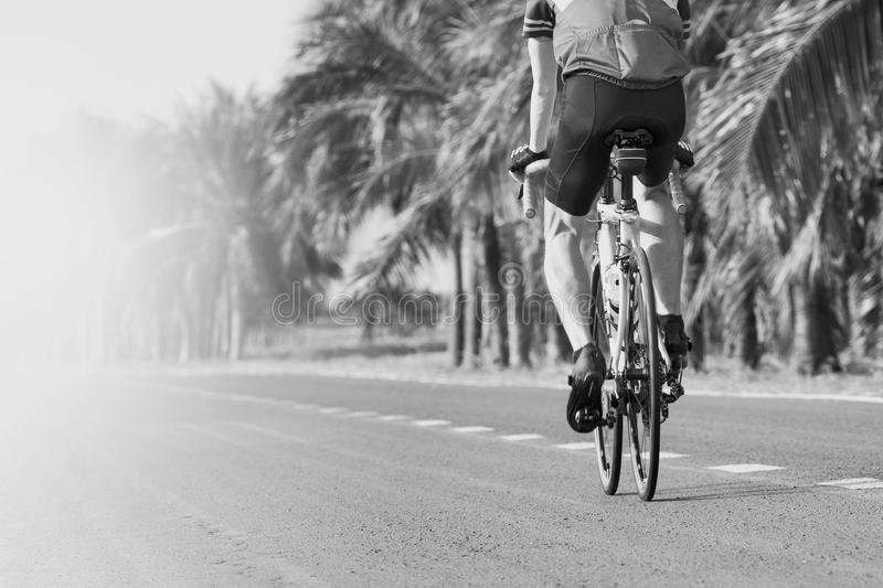 Young man riding road biking bycycle on asphalt track in black a stock images