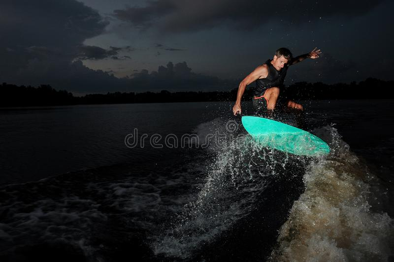 Young man riding on the wakeboard in the deep night. Young active brunet riding on the wakeboard on the blue board in the night on the lake on the background of stock images