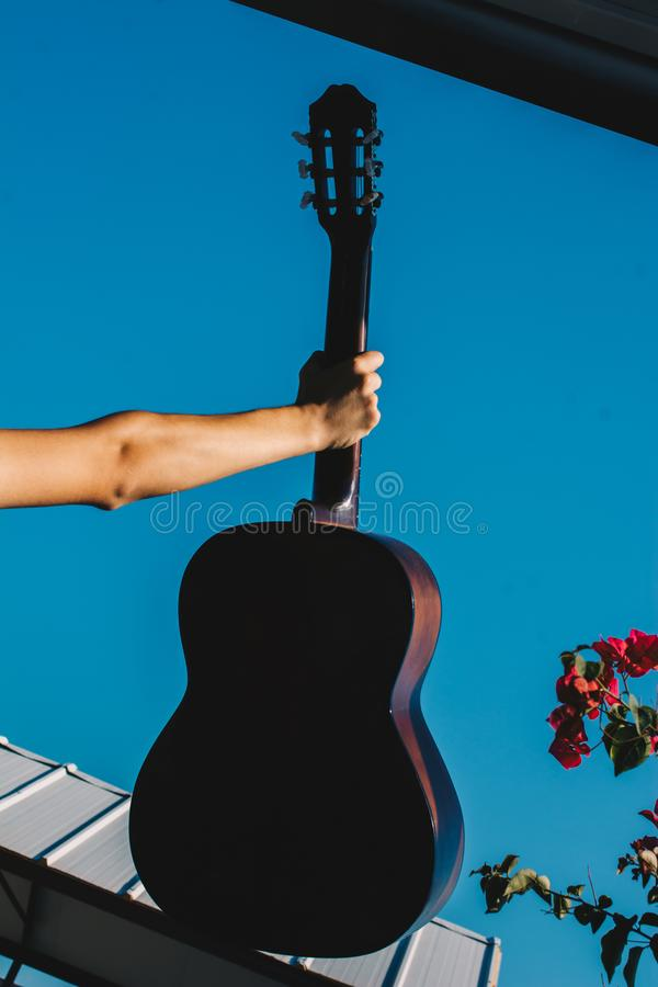 Young man rising an accoustic guitar in the sky. Young man rising an accoustic guitar in the blue sky stock photos