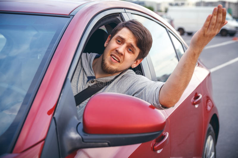 A young man in a road jam. The young man driving the car angry, stuck in a traffic jam royalty free stock image