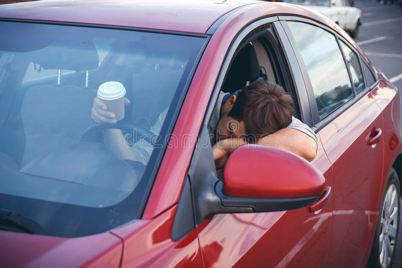 A young man in a road jam. Young man while driving drinks cofee, bored in traffic royalty free stock image