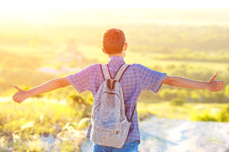 The young man is on the road looking into the distance with a backpack spread his hands to the side the sun`s rays Shine bright royalty free stock photos