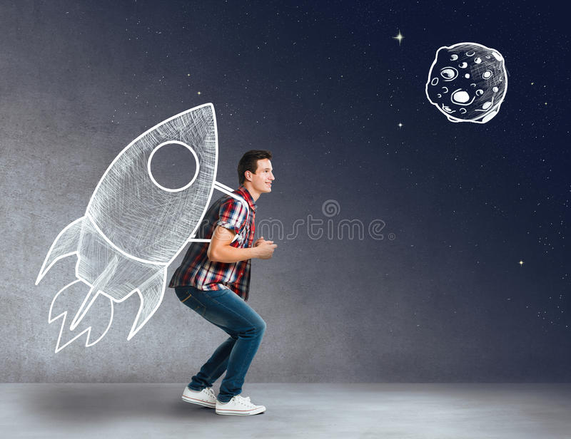 Young man with a rocket on his back stock photo