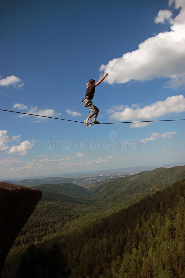 A young man ropewalker balancing over the abyss. A young man rope Walker balancing over the abyss royalty free stock images