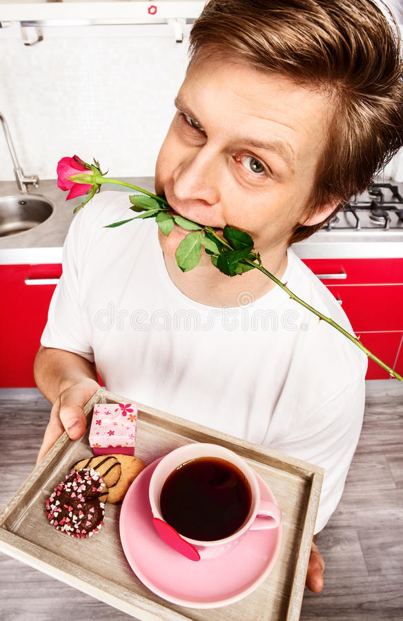 Young man with rose in mouth stock photo