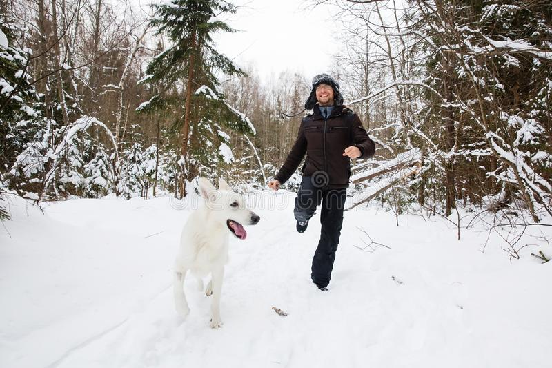 Young man runing in the forest with White dog royalty free stock photo
