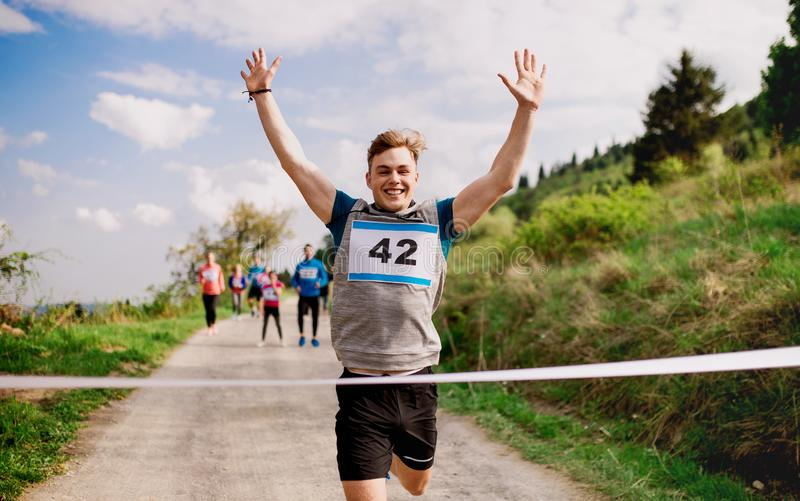 Young man runner crossing finish line in a race competition in nature. A young men runner crossing finish line in a race competition in nature, arms raised stock photo