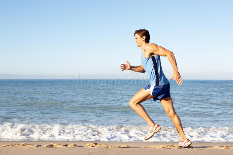 Young Man Running Along Beach royalty free stock images