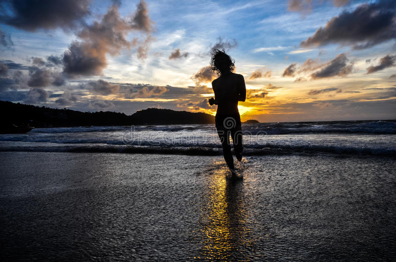 Young man running on beach when sunset. Silhouette of young man running on the beach when sunset, shot on Patong beach, Phuket, Thailand stock image