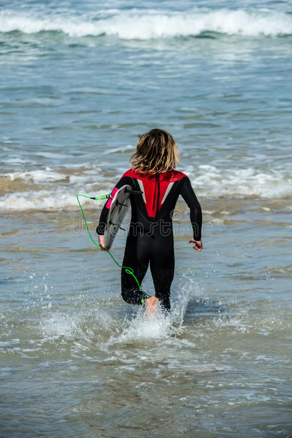 Young man running in surf, Fistral Beach, Newquay, Cornwall. Young man running in surf, Fistral Beach, Newquay, on the stunning North Cornwall coast stock images