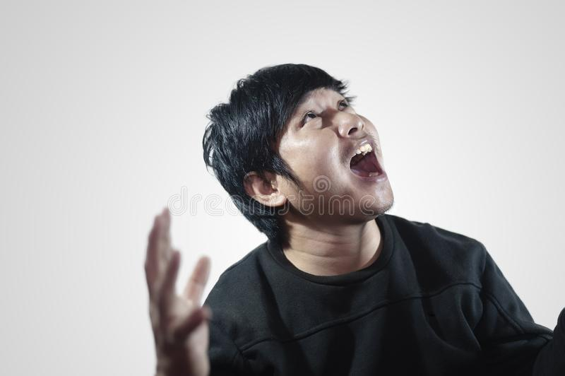 Young man`s face Portrait of a young man screaming and looking up above while standing against. Young man`s face Portrait of a young man screaming and looking stock photos