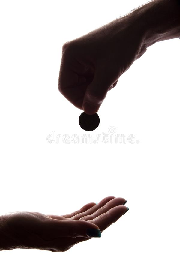 Young man`s hand with a coin gives alms - silhouette, help. Concept royalty free stock photo