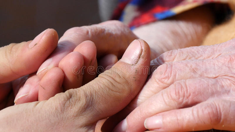 A young man`s hands comforting an elderly pair of hands of grandmother outdoor close-up.Sun comes out from behind the royalty free stock photos