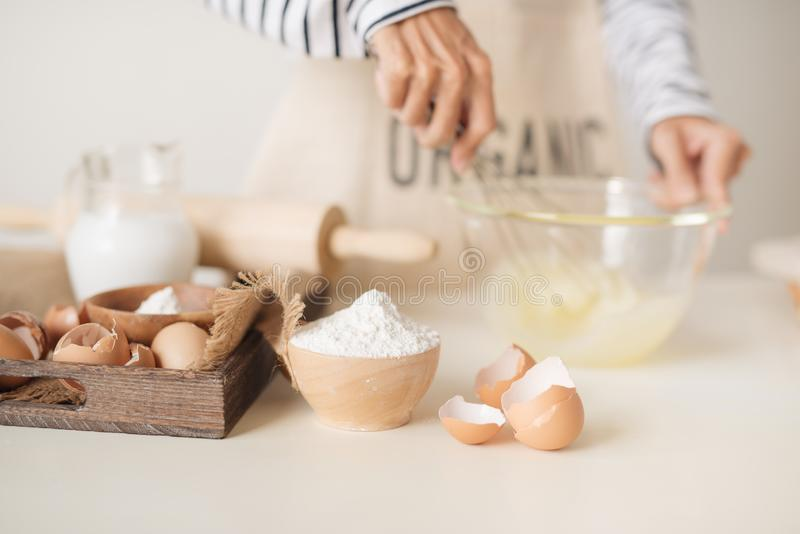 Young man`s hands whisk eggs with sugar to bake fruit cake. Male cooking dough for pie on white table royalty free stock image