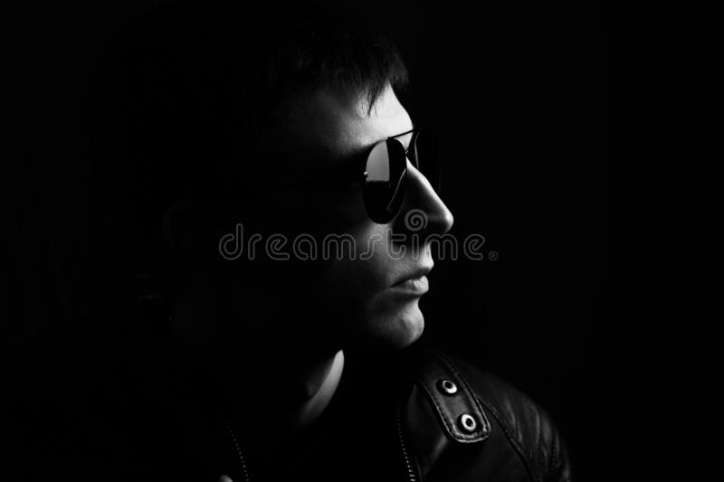 Young man`s portrait. Close-up young man in a black leather jacket and sunglasses royalty free stock image