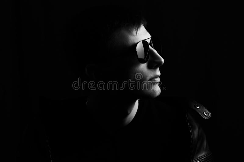 Young man`s portrait. Close-up young man in a black leather jacket and sunglasses stock photography