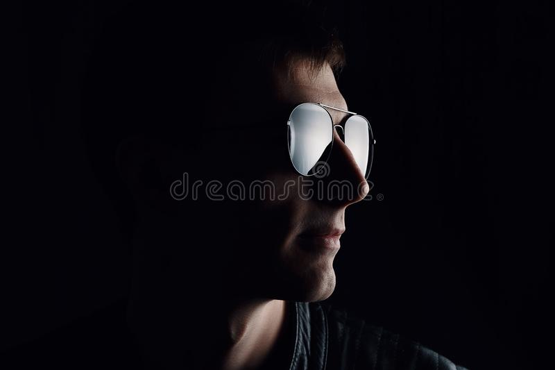 Young man`s portrait. Close-up of serious young man in a black leather jacket and sunglasses stock photo