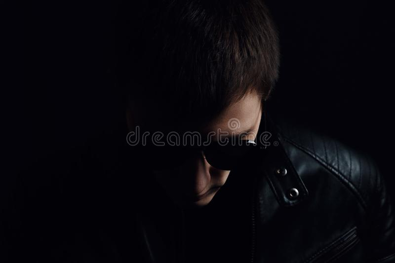 Young man`s portrait. Close-up of serious young man in a black leather jacket and sunglasses stock photography