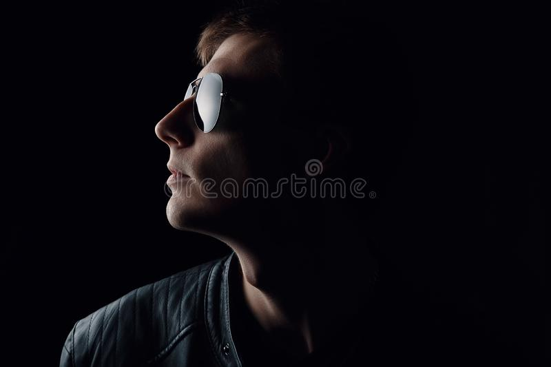 Young man`s portrait. Close-up of serious young man in a black leather jacket and sunglasses on dark background stock photography