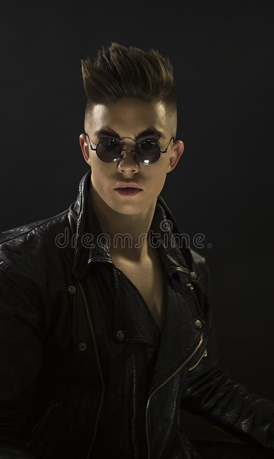Young man`s portrait with round sunglasses. Stylish handsome boy in black leather fashionable rocker-style jacket, Close-up stock photo
