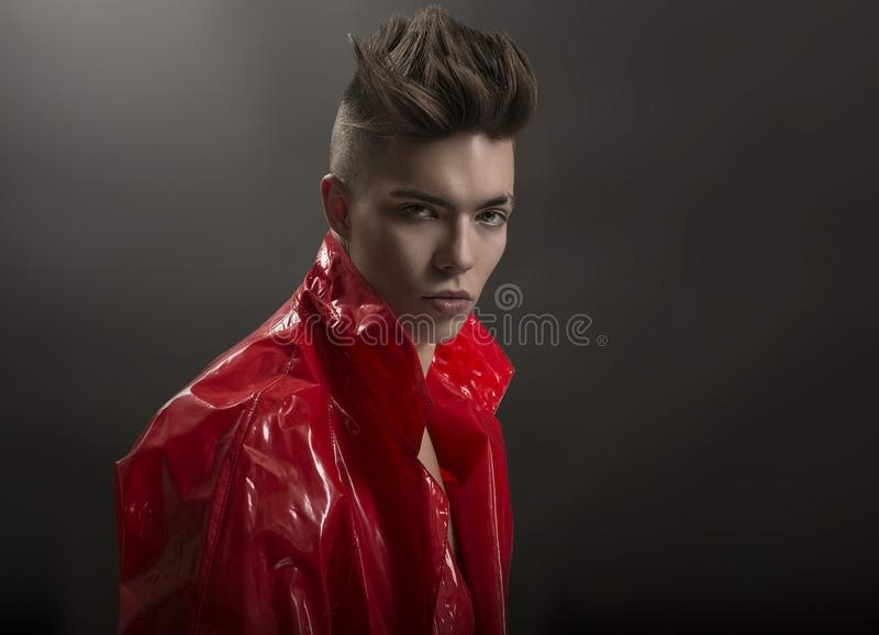 Young man`s portrait. Stylish handsome Guy in fashionable red Long lacquer raincoat, Close-up stock photos