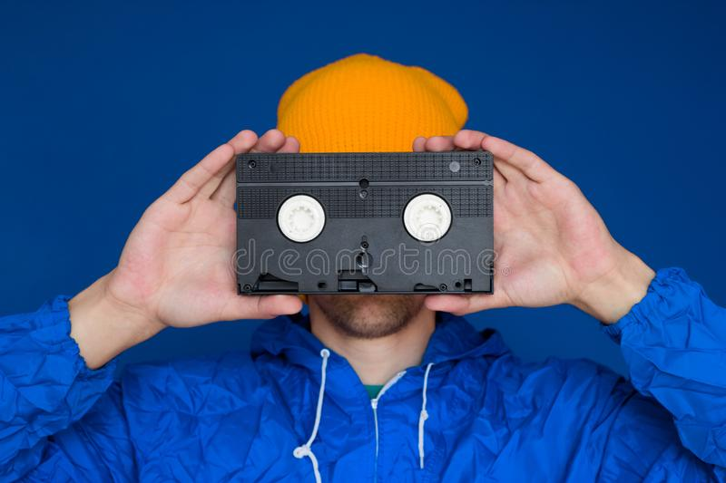 Man  in 90s sports jacket and yellow hat with VHS cassette on blue background. Young man  in 90s sports jacket and yellow hat with VHS cassette on blue stock image