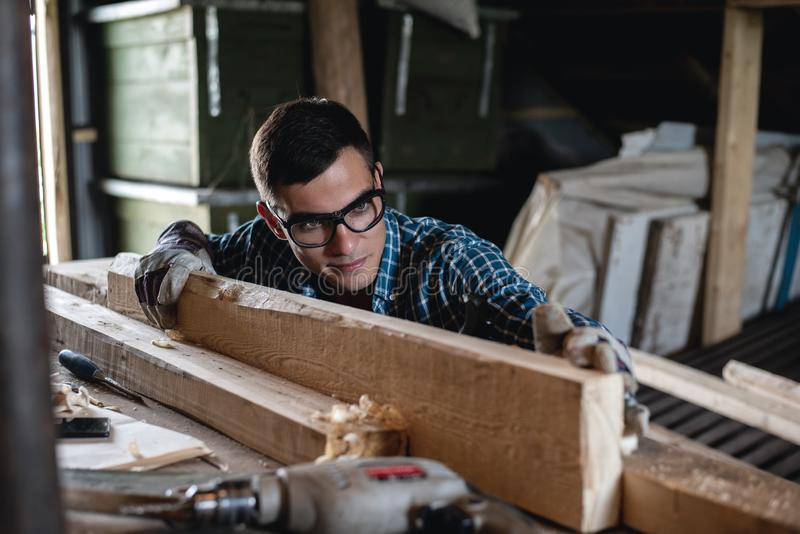 Young man in safety glasses and gloves checks the quality of the planed wooden board royalty free stock image