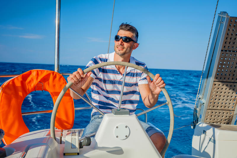 Young man sailing yacht royalty free stock photos