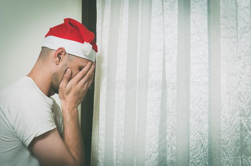 Young man with Santa Claus hat cover his face with his hands and cry near window feeling lonely and sad for New Year and Christmas stock image