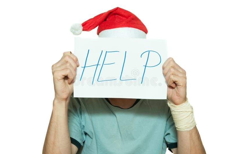 Young man with Santa Claus hat cover his face with help sign after suicidal attempt feeling lonely and sad for New Year and Christ royalty free stock photos