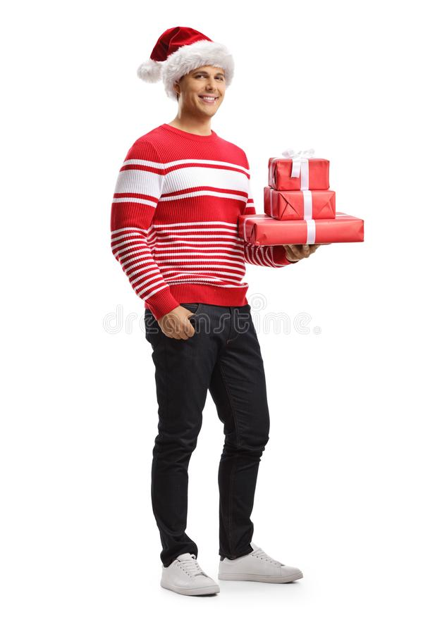 Young man with a santa claus hat holding christmas gifts royalty free stock photos