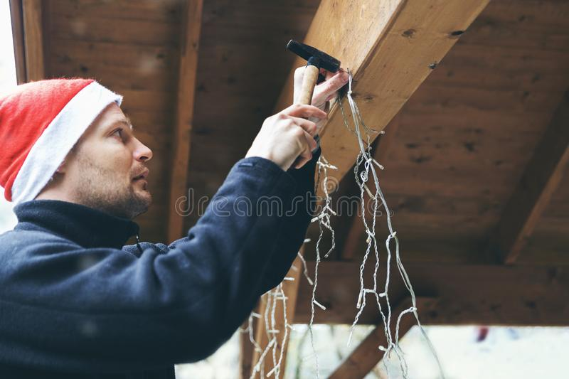 Man with santa hat decorating house outdoor carport. installing christmas lights stock photo
